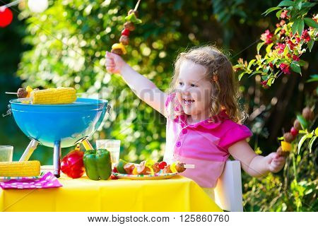 Children grilling meat. Family camping and enjoying BBQ. Little girl at barbecue preparing steaks kebab and corn. Kids eating grill and healthy vegetable meal outdoors. Garden party for toddler child