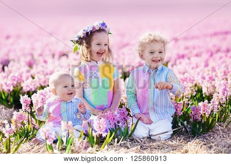 Three children playing in beautiful hyacinth flower field. Little girl toddler boy and baby play in sunny summer garden with purple flowers. Kids having fun outdoors. Brothers and sister together.