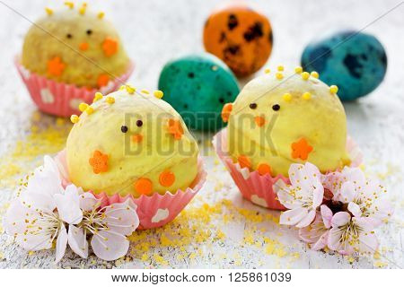 Easter dessert candy in shape of yellow chick in chocolate. Festive treat for children selective focus