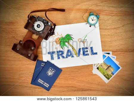 Camera passport and paper with drawing beach holiday concept. Work desk tourist.