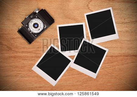 Vintage camera with four blank photo card on wooden table
