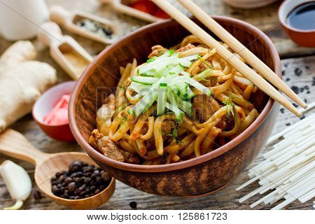 Udon thick wheat noodles with fried meat and sauce selective focus