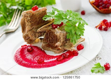Boiled beef on the bone with sauce beet pomegranate fresh parsley on a white table selective focus