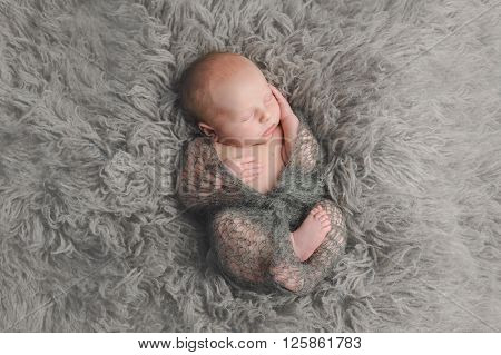 A portrait of a sleeping two week old newborn baby boy. He is swaddled with a knitted mohair wrap and lying on a flokati rug.