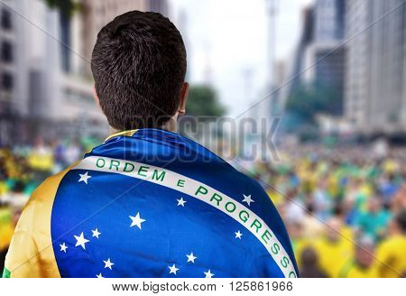 Brazilian holding the flag of Brazil in Paulista Avenue
