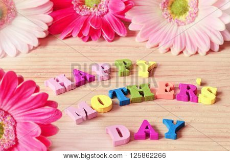 Happy Mothers Day colorful letters spelling greeting on rustic wood table with purple flowers