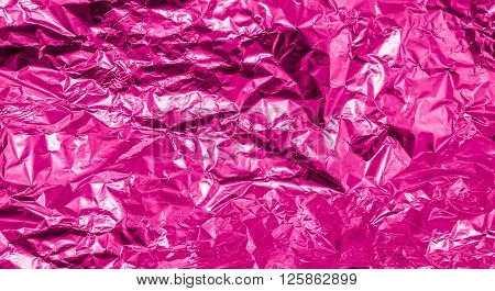 Pink crumpled aluminum foil texture background high contrasted