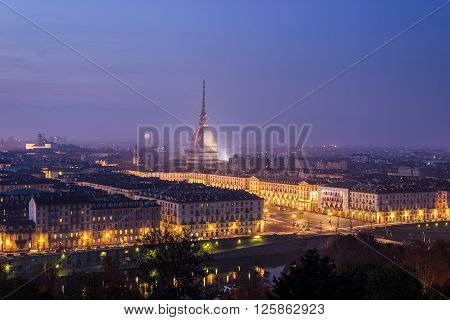Torino (Turin) Piedmont Italy. Cityscape from above with the Mole Antonelliana towering on the city and glowing in the night.