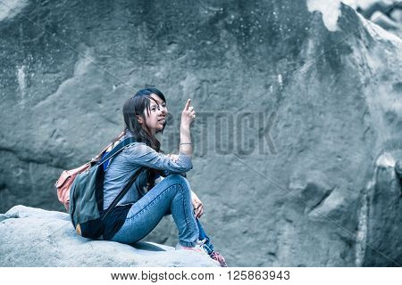 Two young asian women sitting to rest in front of a dark gray wall of rock and talking with gestures by point a finger at something in blue vintage light