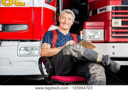 Smiling Firefighter Sitting On Chair Against Trucks