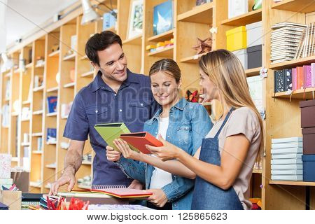 Saleswoman Showing Books To Couple