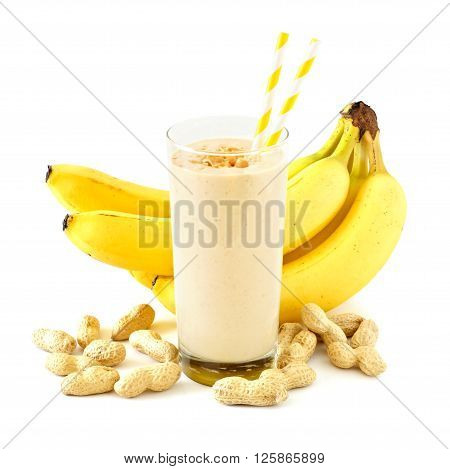 Peanut Butter Banana Smoothie In A Glass With Straws And Scattered Peanuts And Bananas Over White
