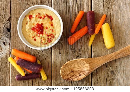 Baby Rainbow Carrots With Hummus Dip And Spoon, Overhead View On A Rustic Wooden Background