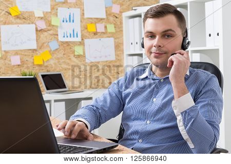 Businessman in headphones with microphone sitting at computer smiling. Office at background. Concept of work.