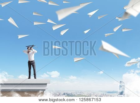 Archer standing on pedestal aiming at paper planes on sky background