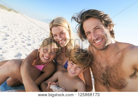 Young family taking selfie in a summer holyday at beach. Portrait of family on summer beach holiday looking at camera. Mother and father with two childreen taking photo at beach.
