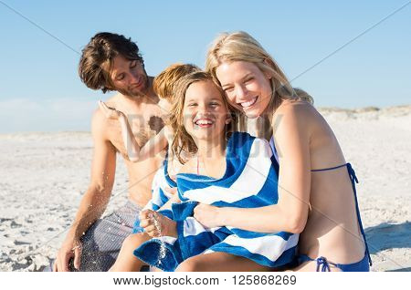 Cute little girl being embraced with a towel by mother. Mother drying daughter with a towel after a swim in the sea. Mother and child embracing after swim.