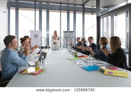 Business people clapping hands after successful meeting  in modern office.