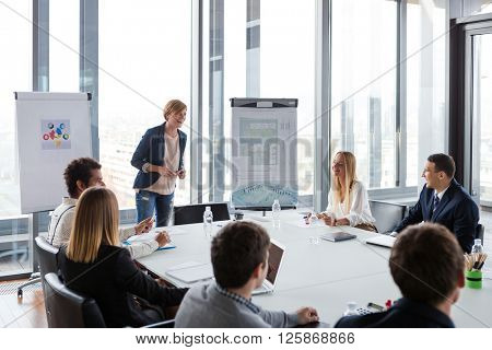 Business people laughing at meeting in modern office.