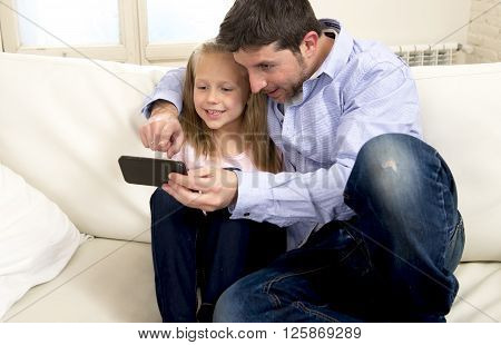 young happy father showing sweet little girl using internet on mobile phone having fun together sharing a beautiful moment dad daughter on home sofa couch in parenting and education technology