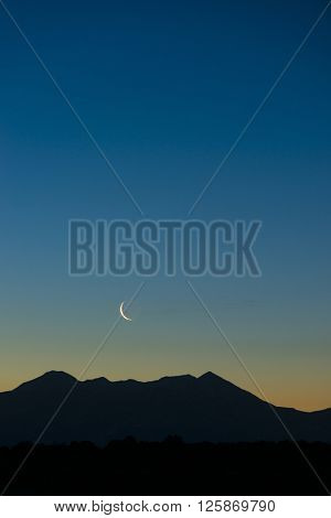 Early morning waning waxing crescent moon rising over graphic silhouetted mountain vertical