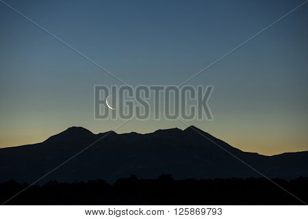 Early morning waning waxing crescent moon rising over graphic silhouetted mountain