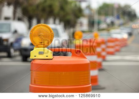 long line of orange traffic barrier barrels to detour traffic around construction zone shallow depth of field