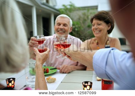 Senior group having a toast during a dinner on a terrace