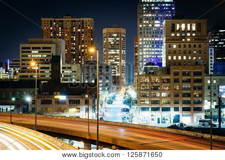 View Of The Jones Falls Expressway And Buildings In Downtown At Night, In Baltimore, Maryland.