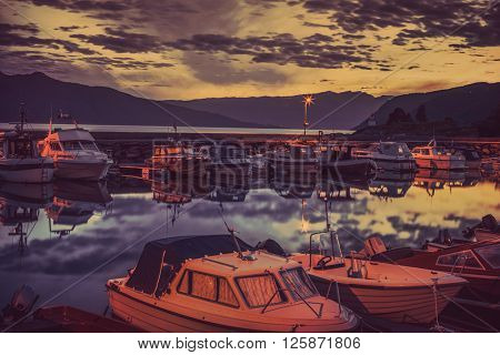Boats in dock. Twilight landscape with soft sunset red tint.