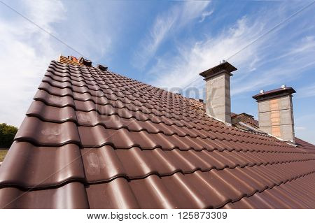 New red tiled Roof with chimneys against the blue sky