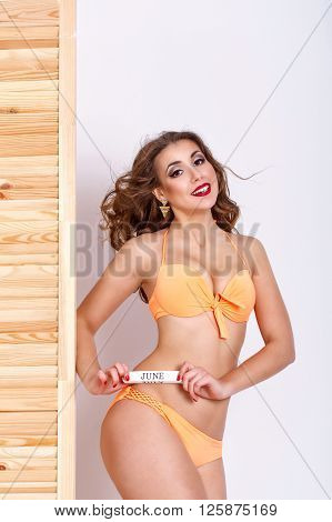 Slender attractive girl in a swimsuit. Girl holds a sign in June. Shopping. Preparation for the beach season.