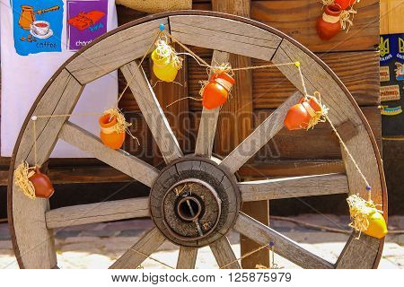 Lviv Ukraine - July 5 2014: Wooden wheel decorated with small earthenware pots on the exhibition sale on Rynok Square in historic city centre