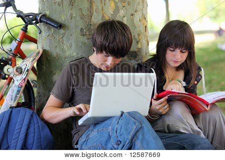 Young boy with a laptop computer sitting near a girl