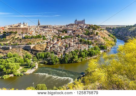 is Alcazar Fortress Churches Cathedral Medieval City Tagus River Toledo Spain. Toledo Alcazar built in the 1500s Destroyed in Spanish Civil War and then rebuilt after war. Unesco historical site; Tagus is longest river in Spain.