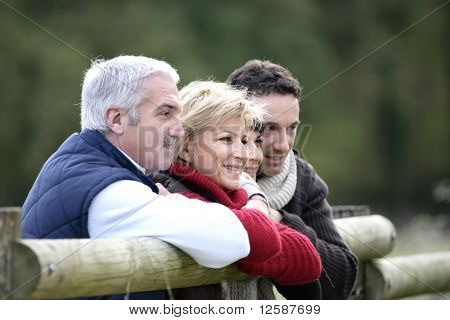 Portrait of men and women leaning on a wooden barrier in the countryside