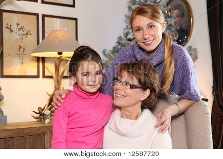 Portrait of a little girl sitting on a senior woman near a young woman