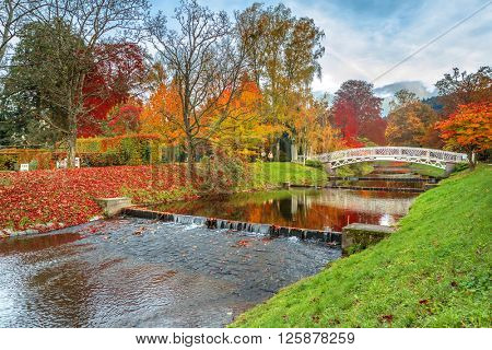 Beautiful autumn landscape with bridge and reflection in river