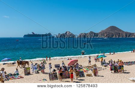 Cabo San Lucas, Mexico- April 27/2016: Vendors sell there wares and services to tourists in front of a resort in Cabo San Lucas as a cruise ship enters the bay.