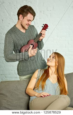 Young man playing ukulele. Beautiful woman listenin in living room.