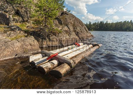 wooden raft at the rocky shore of forest lake