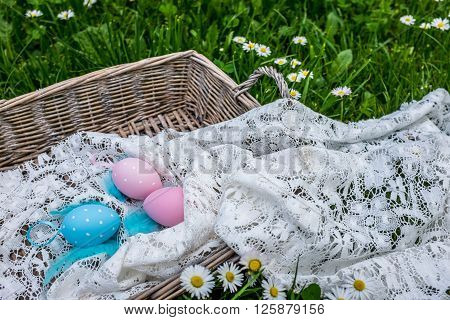 Painted Easter Eggs In Wicker Basket On The Grass