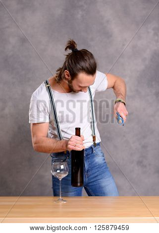 Young Man Opening Red Wine