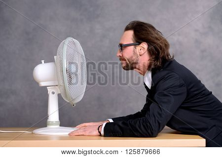 Business Man In Dark Suit Sitting In Front Of Ventilator