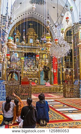 JERUSALEM ISRAEL - FEBRUARY 16 2016: The interior of St James Cathedral with hundreds of oil lamps wooden carved altar covered with gold on February 16 in Jerusalem.