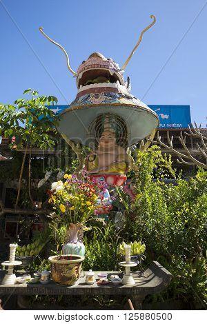 Sculpture of a seated Buddha under the dragon's head. Pagoda Linh Phuoc. Trai Mit, Vietnam