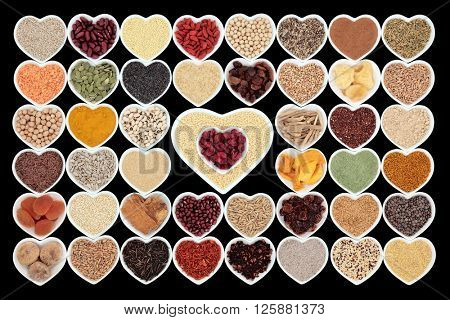 Large dried health food in heart shaped china,bowls over black background. High in minerals, vitamins and antioxidants.