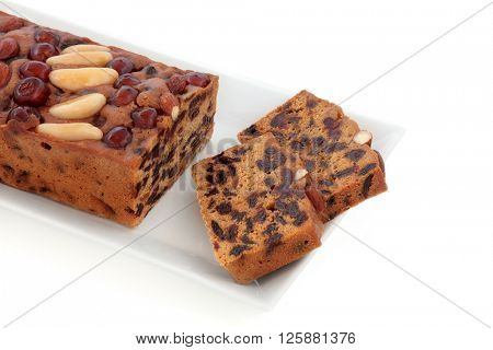 Genoa fruit cake with slices on a plate over white background.