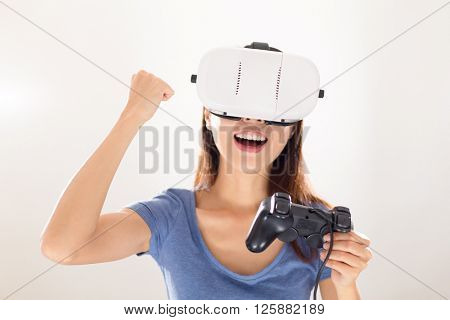 Thrilled Woman wearing virtual reality device and joystick