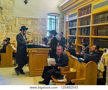 JERUSALEM ISRAEL - FEBRUARY 16 2016: The ultra orthodox worshipers pray sing play the violin and dance in the synagogue at the King David's Tomb on February 16 in Jerusalem